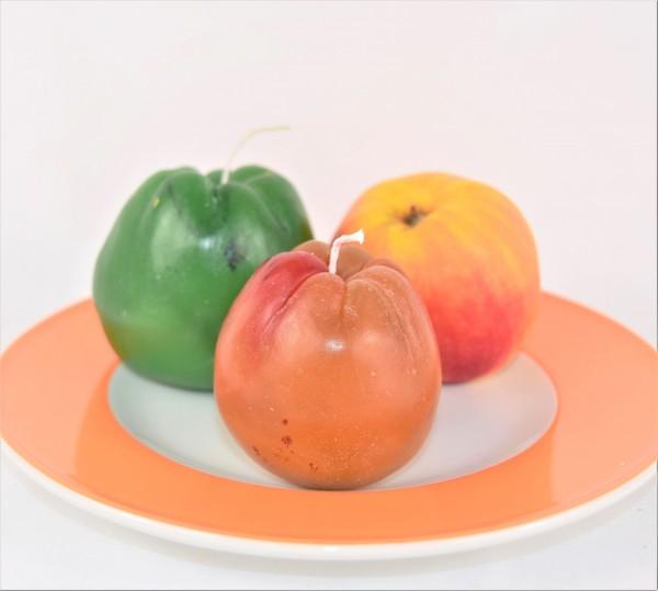 Apfelkerzen auf orangfarbenem Teller